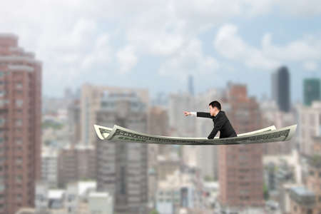 finding: Businessman with pointing finger gesture sitting on money flying carpet, with city buildings background.
