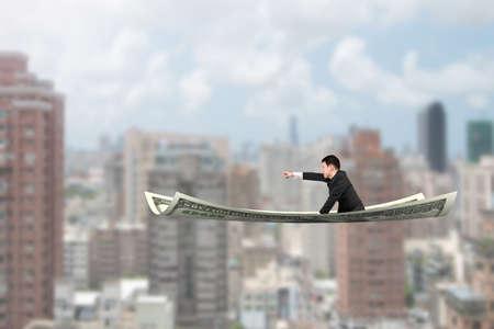 money flying: Hombre de negocios con el gesto que apunta el dedo sentado sobre una alfombra dinero volando, con edificios de la ciudad de fondo.