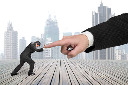 Small man pushing against big other hand forefinger on wooden floor and city skyscraper background.
