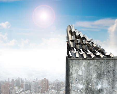 falling down: Businessman stopping the falling of Euro money on top of high concrete wall with sunny sky cityscape. Domino effect and problem solving of concepts