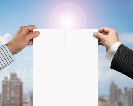 broken contract: Two mans hands holding the tearing contract paper with blank white, on sunlight and city buildings background. Stock Photo