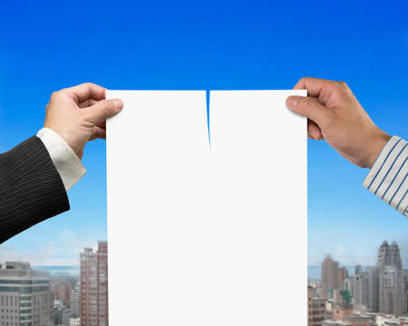 broken contract: Two mans hands holding the tearing contract paper with blank white, on blue sky and city buildings background.