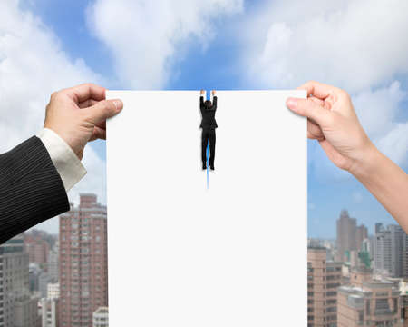 breaking the rules: Man and woman hands holding the tearing contract blank white paper with businessman hanging on it, on clouds sky and city buildings background. Stock Photo