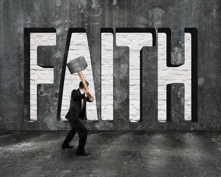 prinitng block: Faith word on concrete wall with man holding hammer, on concrete floor indoors background.