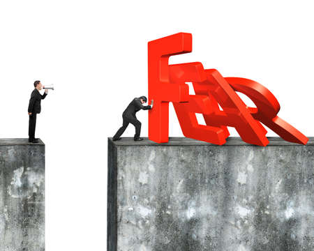 stabilize: Man stopping domino of red fear word falling with another man holding speaker shouting on top of concrete wall, isolated on white background. Stock Photo
