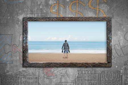 beach window: Old wooden frame window of sea view, with barefoot man holding leather shoes standing on sand beach, on business concepts doodles wall background. Stock Photo