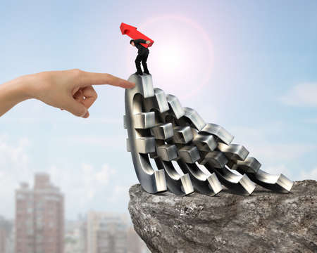 stabilize: Man carrying red arrow up, balancing on falling of Euro currency symbols with big woman hand forefinger helping on cliff, with sunny sky cityscape background. Domino effect and problem solving of concepts.
