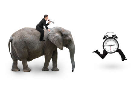Man using speaker riding elephant after alarm clock with human legs running, isolated on white background. Reklamní fotografie