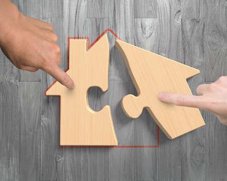 Uomo e donna, due mani di montaggio puzzle di figura della casa di legno, alto angolo di visualizzazione, sullo sfondo di legno della plancia.