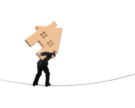 Man carrying wooden house and balancing on tightrope, isolated on white background.