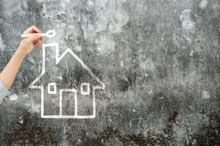 house shape: Woman hand holding chalk drawing house shape clouds on dirty concrete wall.