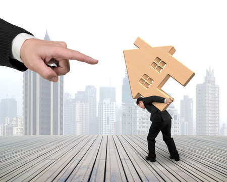rent index: Big hand forefinger pointing at man carrying wooden house on his back, with city skyscraper background.