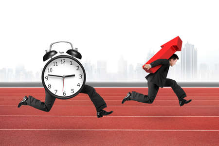 Alarm clock of running legs running after man carrying red arrow up, on red track with concrete wall background. Reklamní fotografie