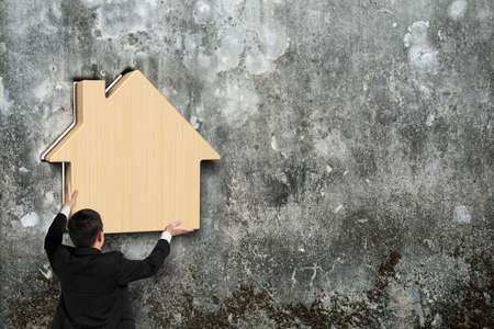 dirty old man: Man putting wooden house into hole of old mottled concrete wall Stock Photo