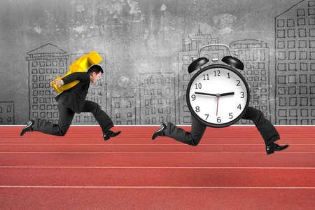 gestion del tiempo: Hombre que lleva el signo de d�lar y corriendo tras el despertador de piernas corriendo, en la pista roja con fondo muro de hormig�n.