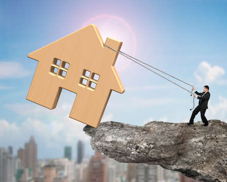 building loan: Man pulling rope to move wooden house on cliff edge, with sun sky cityscape background.