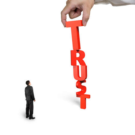 stabilize: Big hand putting T for trust word together, with small businessman looking at, isolated on white background.