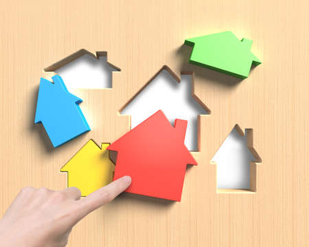 assemble: Different colorful houses suit house shape holes of wooden board, with woman hand index finger pushing one to assemble.