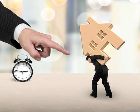 rent index: Businessman carrying wooden house with alarm clock on the table, and big hand forefinger pointing at, on blurred background. Stock Photo