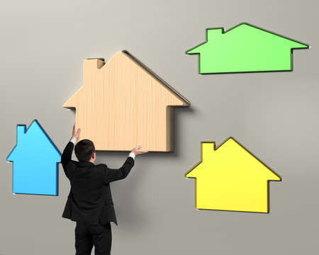 pursue: Man hands putting wooden house in suitable hole, with different colorful houses.