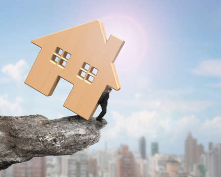 heavy risk: Man holding wooden house on cliff edge, on sunny sky cityscape background. Stock Photo
