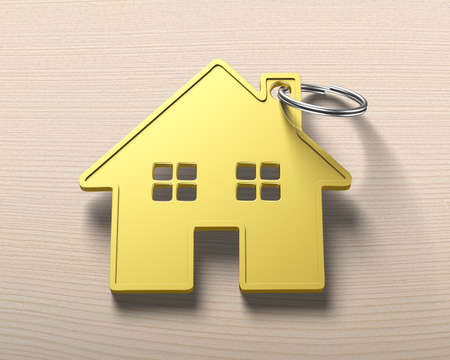 gold house: Gold house shape key ring, on wooden table background. Stock Photo