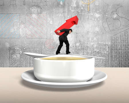 risks ahead: Man carrying red arrow up and balancing on spoon with soup bowl on the table, with concrete wall background. Stock Photo
