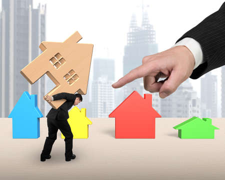 forefinger: Businessman carrying wooden house on the table, with big hand forefinger pointing at, on city skyscraper background.