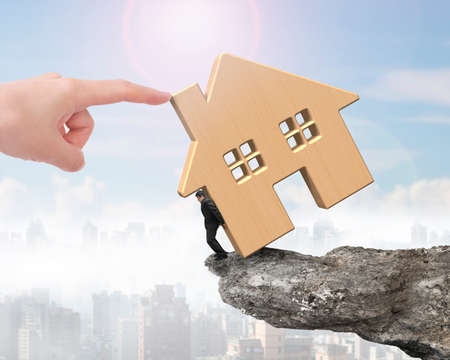 rent index: Man holding wooden house on cliff edge with another big hand pushing, on sunny sky cityscape background.