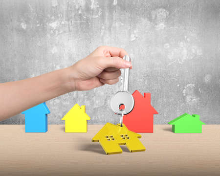 appropriate: Woman hand holding silver key with golden house shape keyring, and four different colorful houses on table, with concrete wall background. Stock Photo