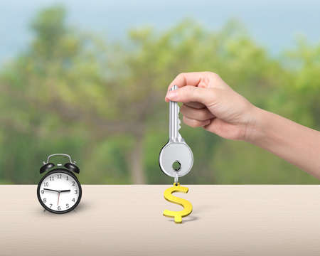 safekeeping: Woman hand holding silver key with golden dollar sign shape keyring, and alarm clock on the table.