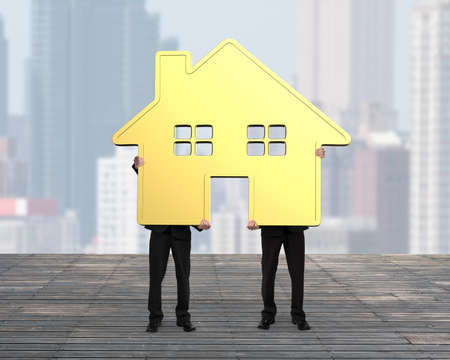 gold house: Two businessmen holding gold house together on wooden floor, with city buildings background.