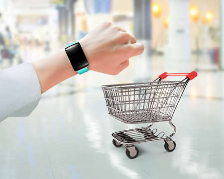 Woman hand wearing smart watch with small shopping cart, on blurred background, limited time shopping concept.