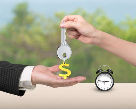 safekeeping: Woman hand giving silver key with gold dollar sign shape keyring to man hand, and alarm clock on the table. Stock Photo
