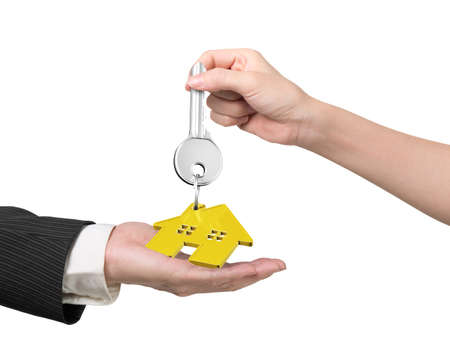gold house: Woman hand giving silver key with gold house shape keyring to man hand, isolated on white background.