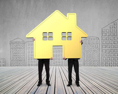 gold house: Two businessmen holding gold house together on wooden floor, with city buildings doodles concrete wall background.