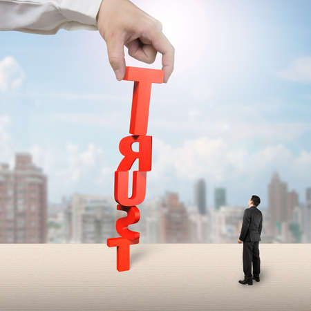 stabilize: Hand stacking TRUST with businessman looking up, on table city view background Stock Photo