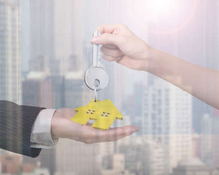 gold house: Woman hand giving silver key with gold house shape keyring to man hand, on city buildings background.