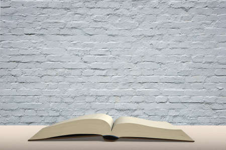 brick wall background: Open book on wooden table with brick wall background nobody empty