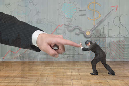 forefinger: Small man pushing against big man hand forefinger, with business concept doodles wooden wall background.
