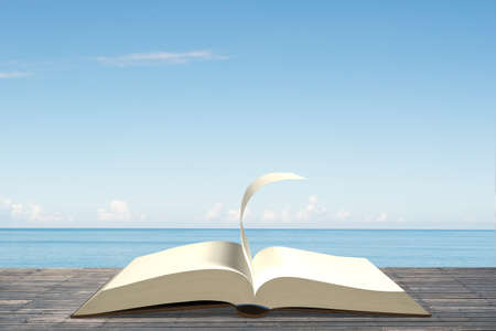 turning: Opening book on old wooden table with turning page, ocean blue sky in sunny windy day