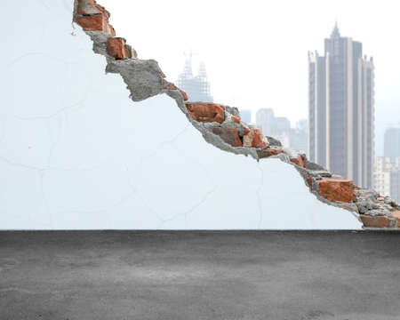 undermine: White crack bricks wall with city building background and dirty concrete floor Stock Photo