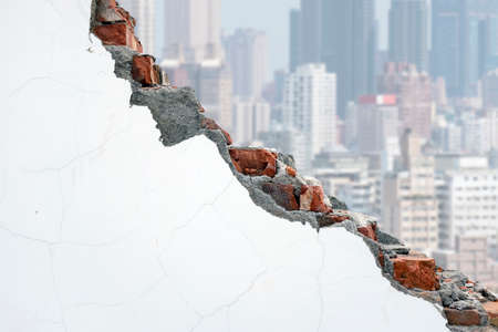 undermine: Cracked white bricks wall with crowded city building background Stock Photo