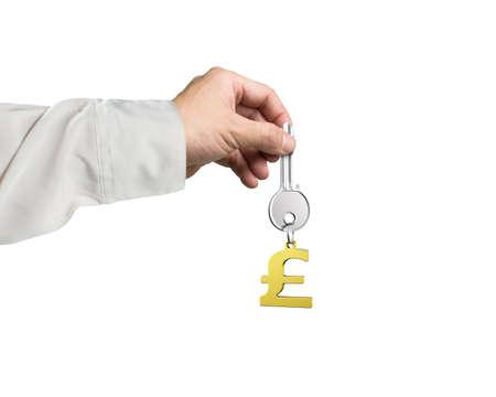safekeeping: Man hand holding silver key with golden pound symbol shape keyring, isolated on white background.