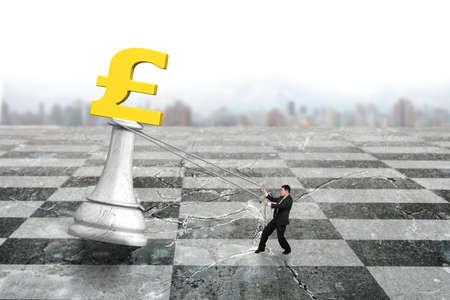 pulling money: Man pulling pound symbol of money chess on chessboard, with urban scene skyline background. Stock Photo