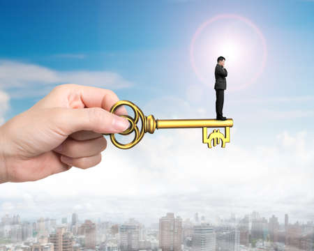 clave sol: Man standing on treasure key in Euro sign shape with hand holding, on sun sky urban scene background. Foto de archivo