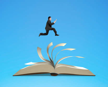 Man holding tablet running on top of flipping pages of open book isolated on blue background.