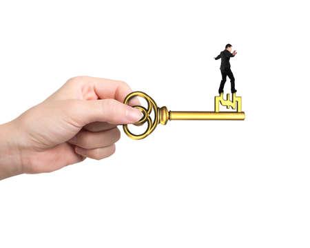 uk money: Man balance on treasure key in pound sign shape with hand holding, isolated on white background.