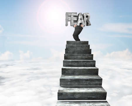 Businessman carrying big 3D fear concrete word on top of concrete stairs, with sky sun clouds background. Stock Photo