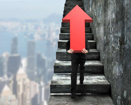 Businessman carrying big 3D red arrow sign and climbing on concrete stairs, with city buildings background.